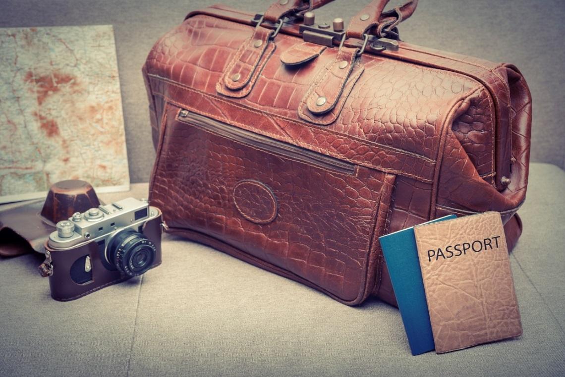 Mala de viagem ao lado de um passaporte e um mapa de viagens