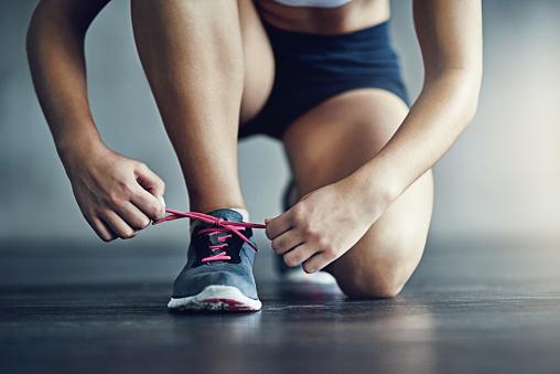 Mulher amarra os cadarços de seu tênis de corrida