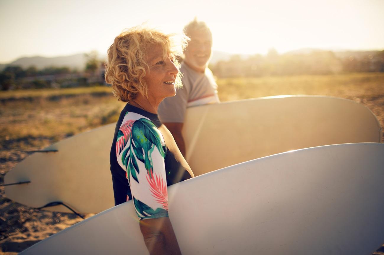 Casal de idosos carrega pranchas durante o pôr do sol na praia